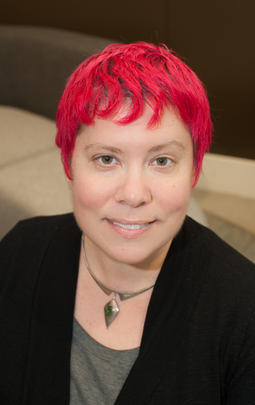 Torrey Podmajersky, a pale-skinned woman with reddish-pink hair, wearing a gray shirt, black sweater, and silver necklace, looking at the camera with a slight smile.